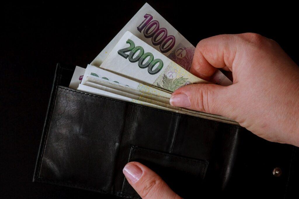 Žena vybírá peníze z peněženky na poplatky